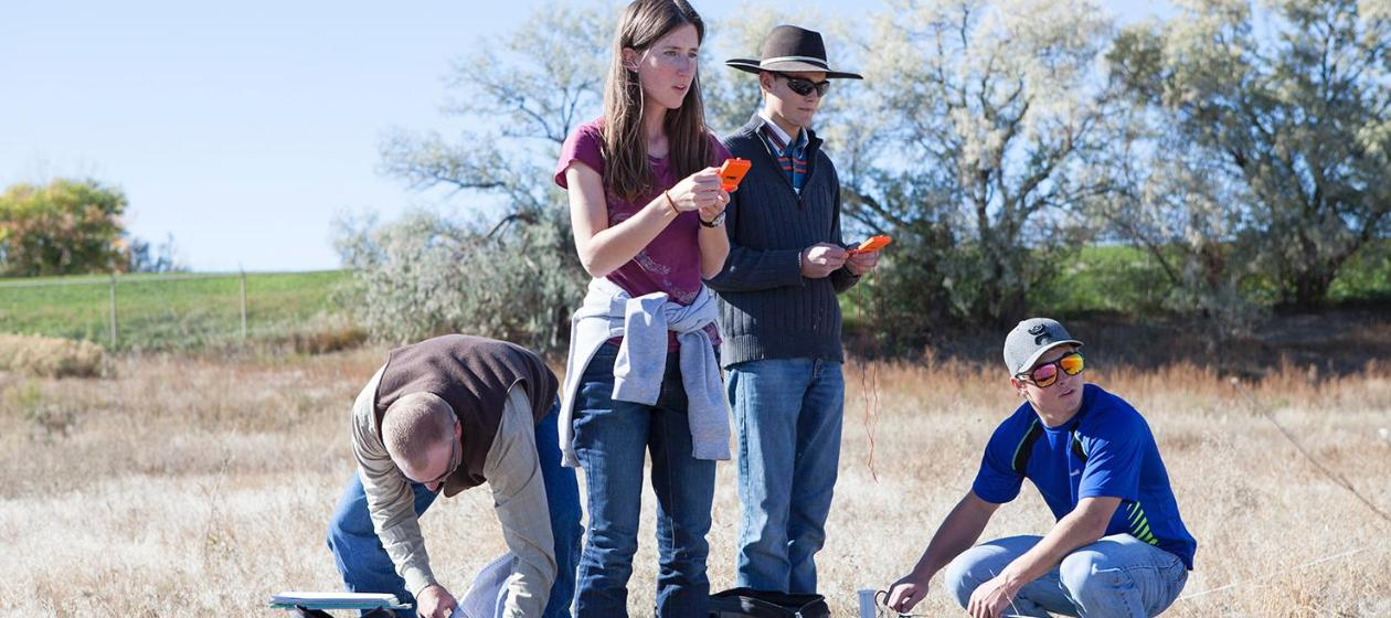 Four students outdoor in the sun surveying a field
