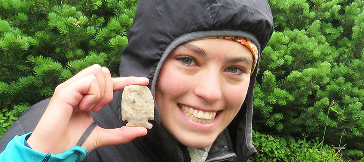 A student uncovers an arrowhead on an archaeological dig.