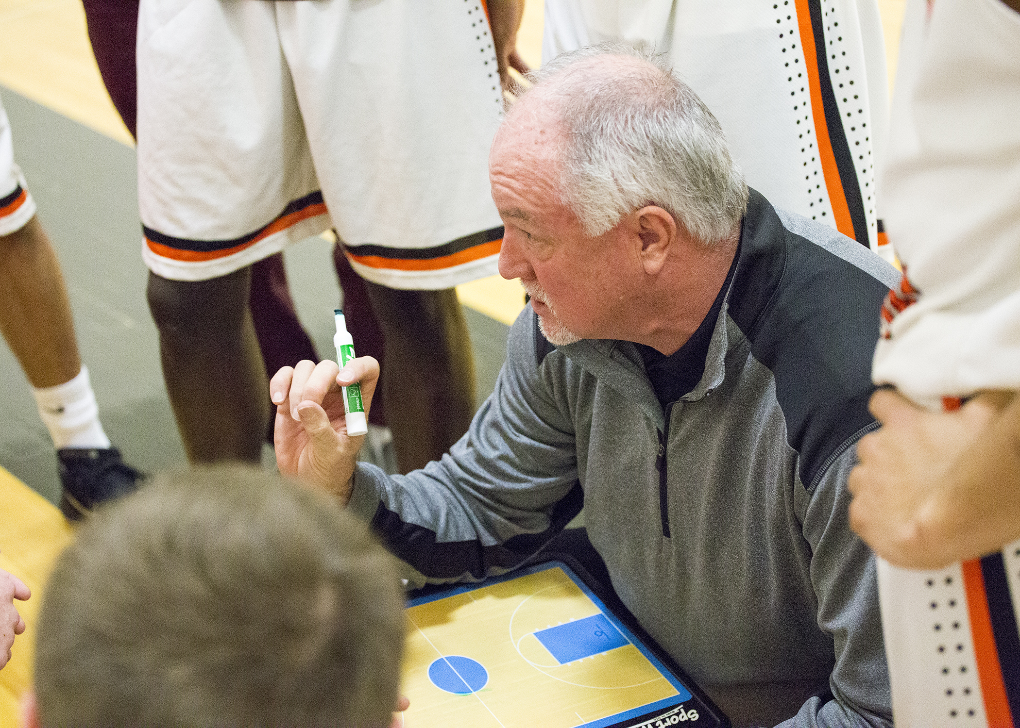 Coach Pat Rafferty showing a play to his basketball team