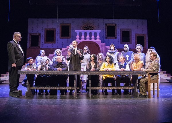 CWC Addams Family cast around a table on stage