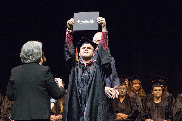 HEQ graduate holds his diploma above his head