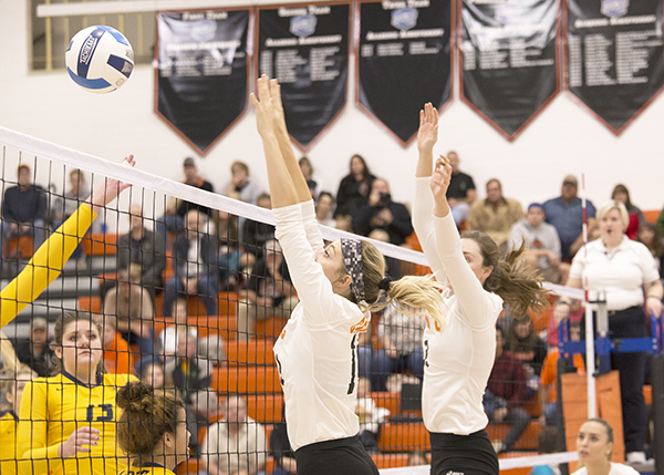 Two CWC volleyball players block the ball at the net