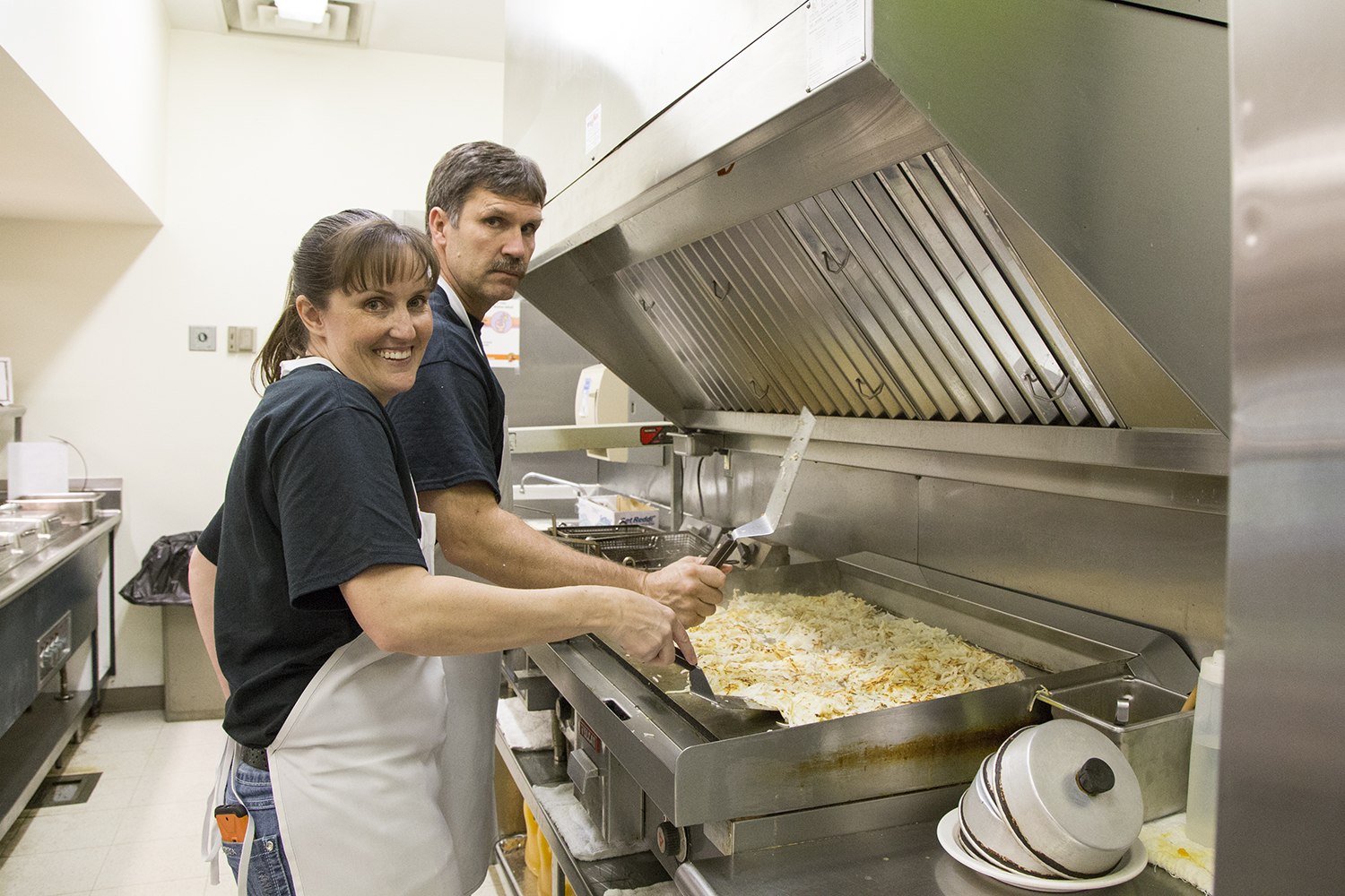 Jennifer Kellner and Steve Barlow cook up hashbrowns for the students.