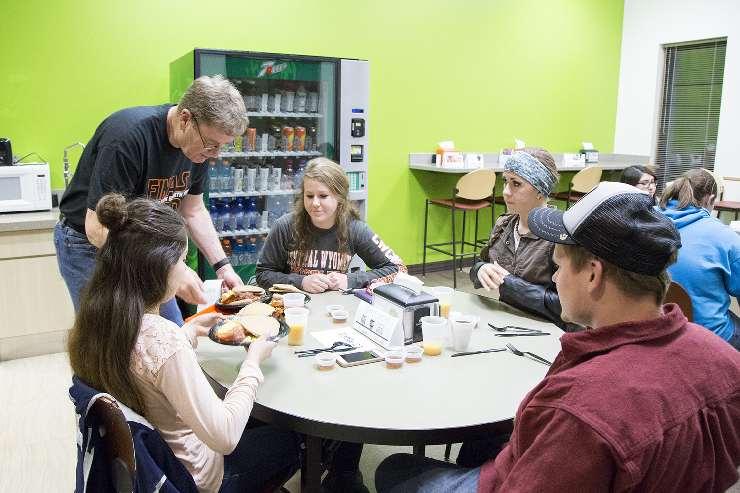 Steve McAllister serves plates of food to students