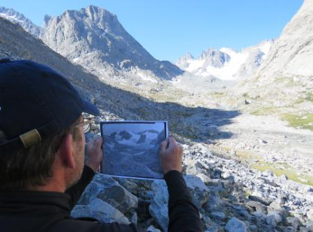 CWC ICCE student compares a historical photo with the location he is in, in the Wind River Mountains