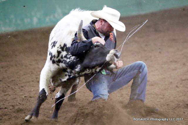 photo of CWC rodeo cowboy Kyle Choate grasping a steer by the horns in the steer wrestling event