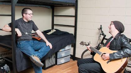 Two guys hanging out in a dorm room with a guitar